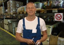 Toni in einem weißem Hemd und blauer Latzhose vor einem Lagerregal