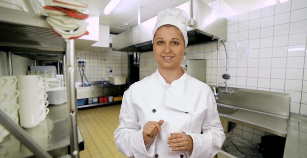 Beata steht in der weißer Küchenkleidung mit Kochmütze in einer Großküche